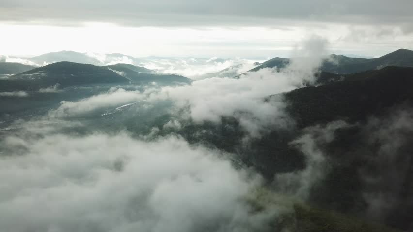 Aerial Fabulous Epic landscape chain of mountains covered white clouds dense fog. Untouched wild open space horizon.  | Shutterstock HD Video #1020127396