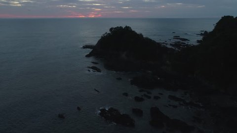 Dark sunrise pull up reveal over the ocean and mountains with rocky coast in rural Japan