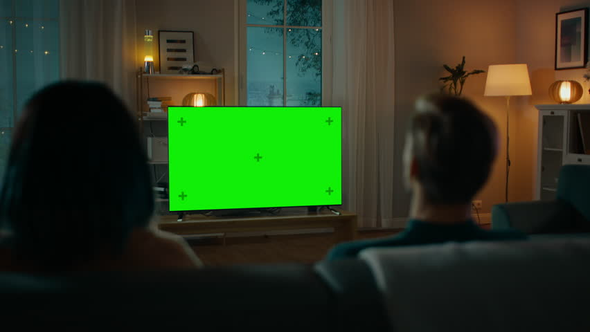 Couple Watches Green Mock-up Screen TV while Sitting on a Couch in the Living Room. Romantic Evening for Boyfriend and Girlfriend. #1020144166