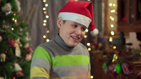 63574f0ea4430 A boy teenager in a hat Santa Claus is dancing near the Christmas tree.  Christmas