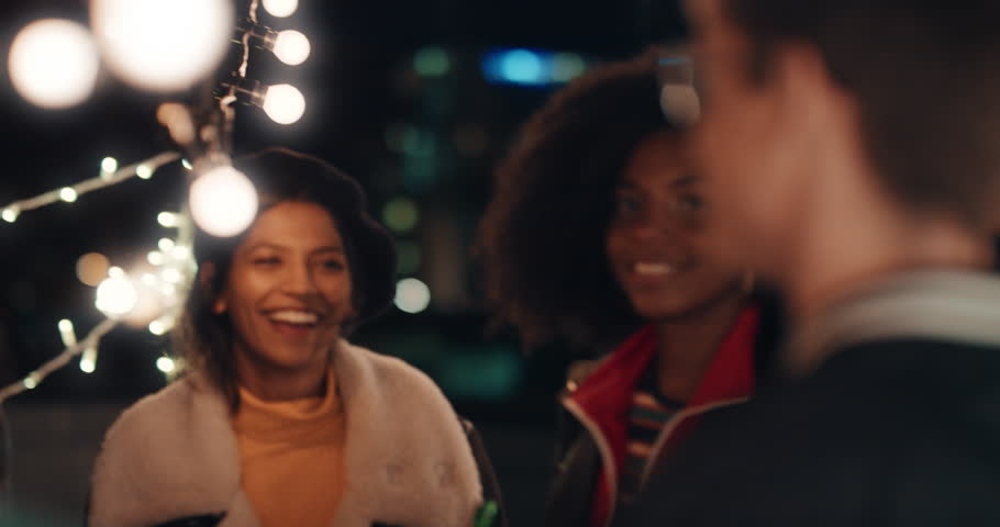 Happy group of friends dancing to lively rooftop party music enjoying weekend celebration in urban city at night | Shutterstock HD Video #1020197446