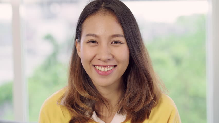 Asian woman feeling happy smiling and looking to camera while relax in her living room at home. Beautiful Asian young female using relax time at home concept.   Shutterstock HD Video #1020201676