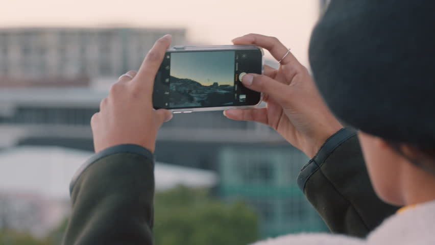 young woman taking photos of city using smartphone mobile camera enjoying sightseeing sharing vacation pictures on social media
