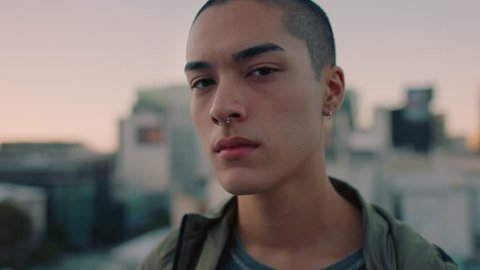 portrait attractive young mixed race man with shaved hair on rooftop at sunset wearing piercings looking confident in urban city background