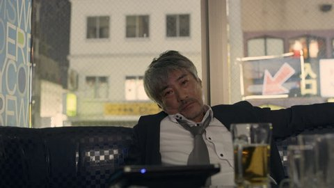 Drunk sad Japanese man sitting at a booth in a karaoke room alone with soft interior lighting. Medium shot on 4k RED camera.