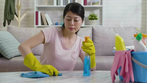 fast motion of young lady trying hard removing dust from the table and feeling tired wiping sweats relaxing a while and keep on doing housework. unhappy housewife unsatisfied cleaning house.