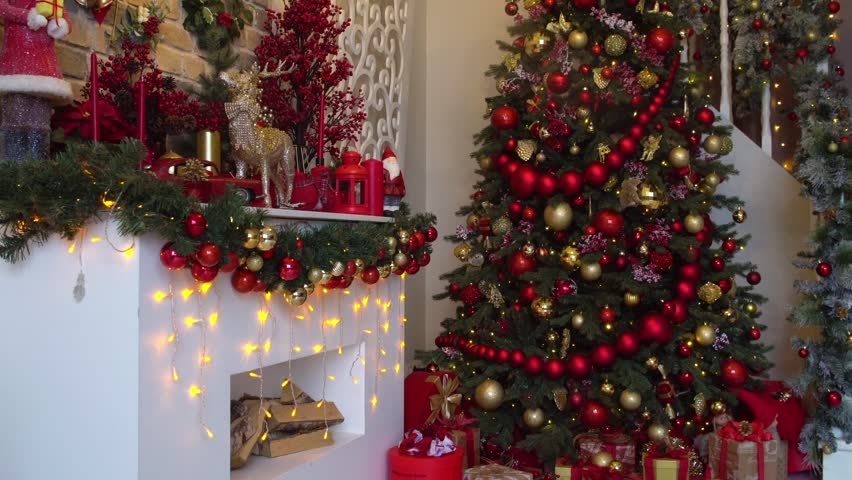 White room interior in red tones with New Year tree decorated, present boxes and artificial fireplace | Shutterstock HD Video #1020261136