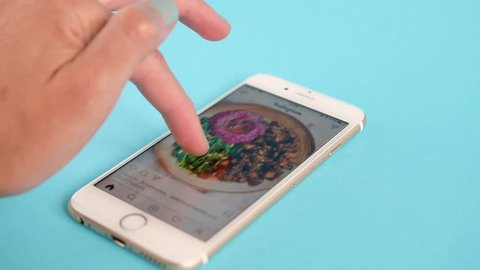 Belgrade, Serbia - November, 2018: Video of Apple Iphone 6s, showing the user scrolling Instagram feed and liking food photos, on light blue pastel background. Girls hand with grey nail color.