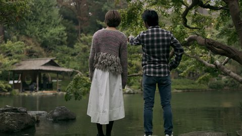 Nervous Japanese man looks out across a pond with his girlfriend and proposes to her in a beautiful garden in the rain with soft natural lighting. Wide shot on 4k RED camera.