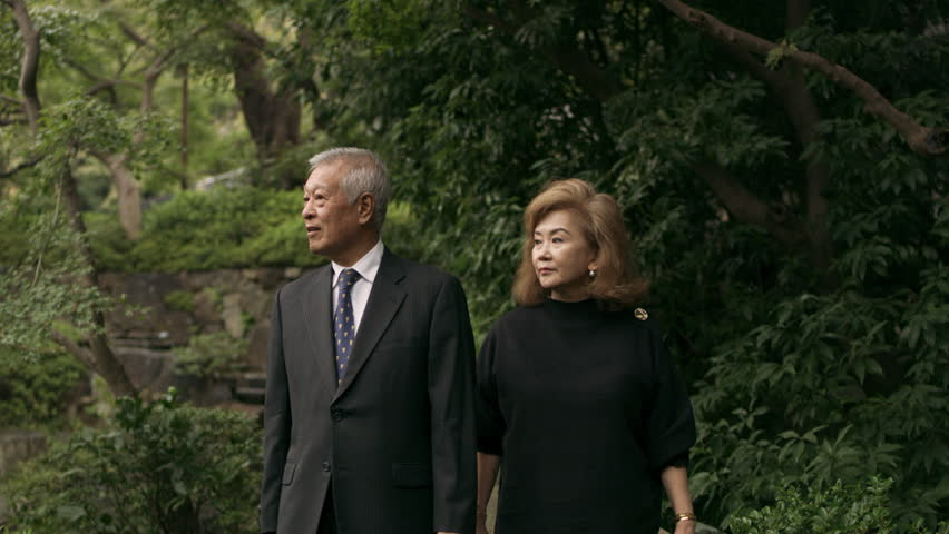 Sad elderly Japanese couple walking in a beautiful green garden with soft natural lighting. Medium shot on 4k RED camera.