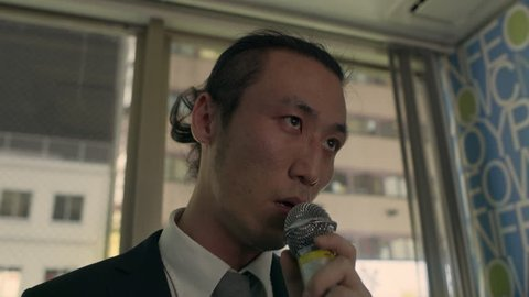 Somber, drunk Japanese man standing alone in a karaoke room and singing a song with a microphone with soft interior lighting. Close up shot on 4k RED camera.