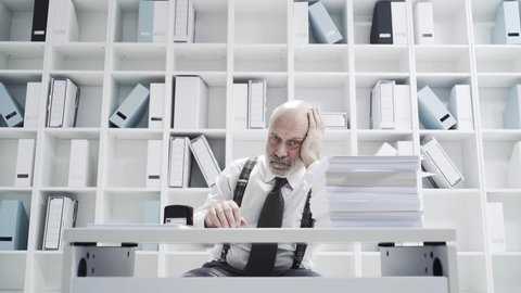Office worker doing a boring repetitive job like a robot: he is stamping documents and staring at the camera