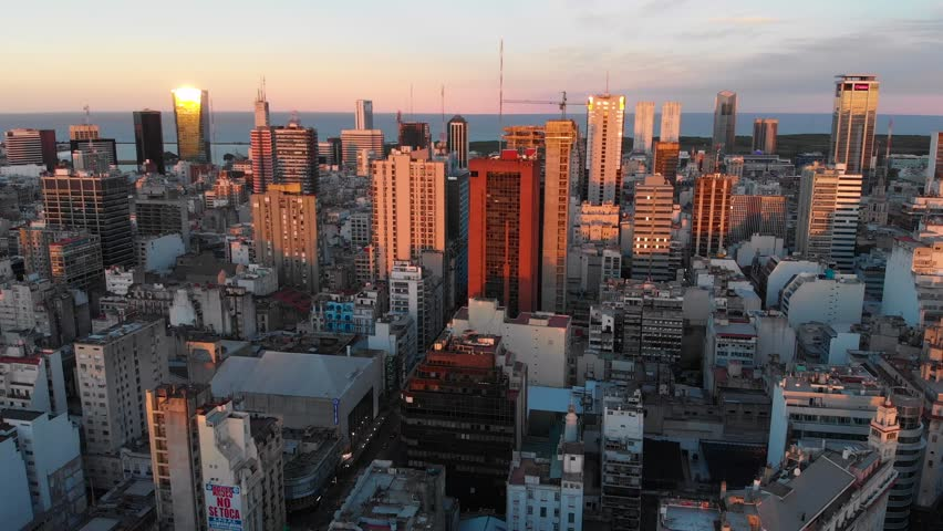 Panoramic aerial drone view of Buenos Aires city downtown in late afternoon over skyscraper buildings, cars and traffic visible in the streets below. Puerto Madero and San Telmo in the background.   Shutterstock HD Video #1020370306