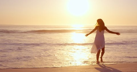 Free happy woman spinning arms outstretched enjoying nature dancing on beach at sunset slow motion RED DRAGON