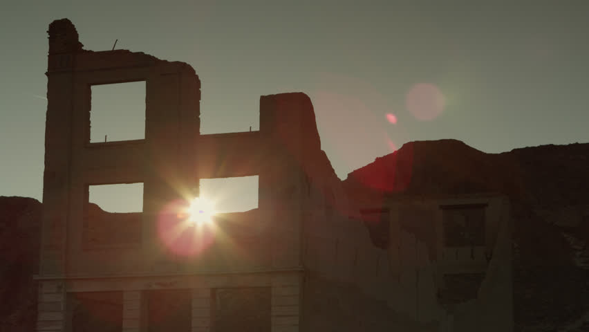 The Setting Sun Desert and a Companion Jet Contrail Peek through an Upper Window of the Famous Cook Bank Ruins in Rhyolite, Nevada | Shutterstock HD Video #1020436576
