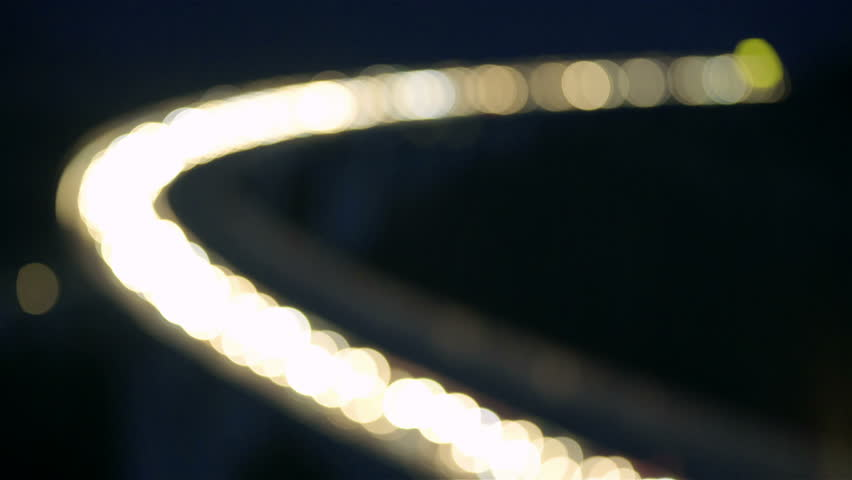 Blurred highway curve with vehicles lights shining HD. Wide shot of curved bridge with a lot of cars slowly moving with bright headlights. | Shutterstock HD Video #1020443266
