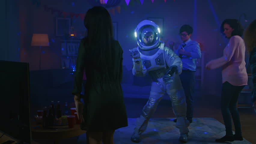 At the College House Costume Party: Fun Guy Wearing Space Suit Dances Off, Doing Groovy Funky Robot Dance Modern Moves. With Him Beautiful Girls and Boys Dancing in Neon Lights. In Slow Motion. #1020541636