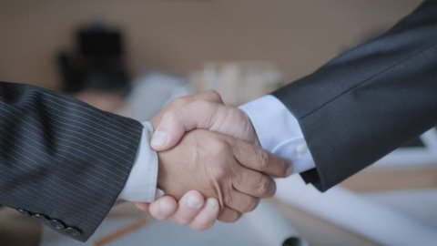 Business people at work in office during conference. Businessmen giving handshake for new agreement after meeting in executive room. Manager and colleague shaking hands and looking at project plans