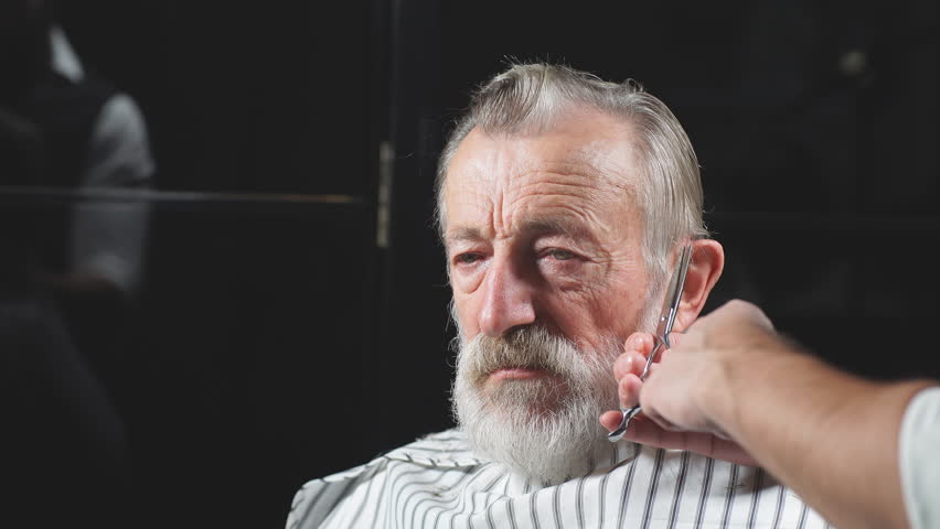 Hairdresser s work for a handsome respectable old-aged bearded man at the barber shop. He is doing styling with the electric shaver. | Shutterstock HD Video #1020589036