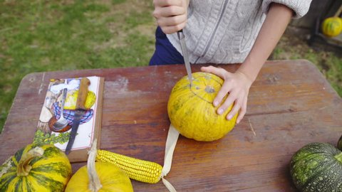 Person cut pumpkin with knife on table HD. Jib shot from top of table with person cutting in to big orange pumpkin to make a scary Halloween head. Using sharp knife.
