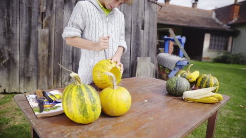 Zoom in while stabbing sharp knife in to empty pumpkin HD. Young person in woolen sweater on old farm working on making a Halloween pumpkin face with knife on brown table.
