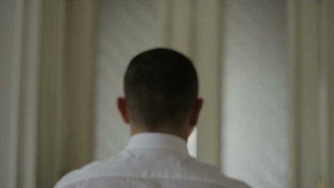 Close-up of a Man in white shirt opening white door. Man pushes the door, enters a long corridor and walks towards a window.