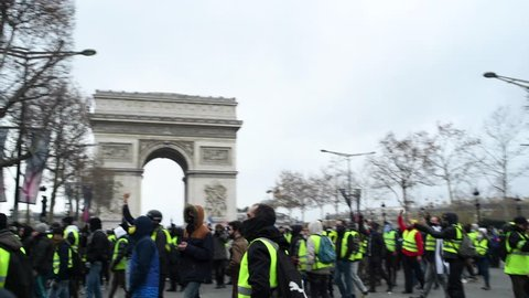 """Paris, France - December 8, 2018. Protesters chant """"Macron  démission"""" (Macron resign) during a Yellow Vests (Gilets jaunes) protest against living costs and rising oil prices on the Champs Elysees"""