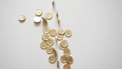 Slow motion. Shiny one British pound coins rolling into the frame and falling onto the pile