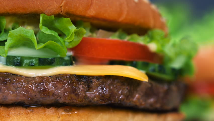 Big appetizing burger with meat cutlet, vegetables, cheese, lettuce and sauce. Hamburger rotates on other meal background, close-up view. Unhealthy yummy food concept. | Shutterstock HD Video #1020717646