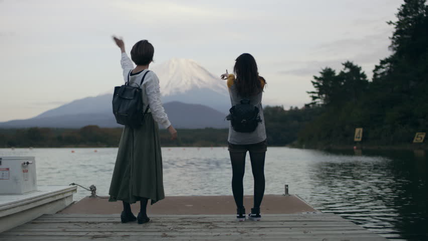 Medium shot on 4k RED camera. Excited Japanese women running up a dock on the water to see Mount Fuji and happily waving at it with soft natural lighting. | Shutterstock HD Video #1020782536