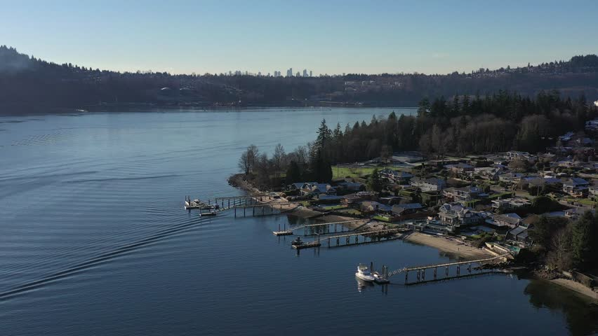 Aerial view over Burrard Inlet, ocean and island with boat and mountains in beautiful British Columbia. Canada. | Shutterstock HD Video #1020790456