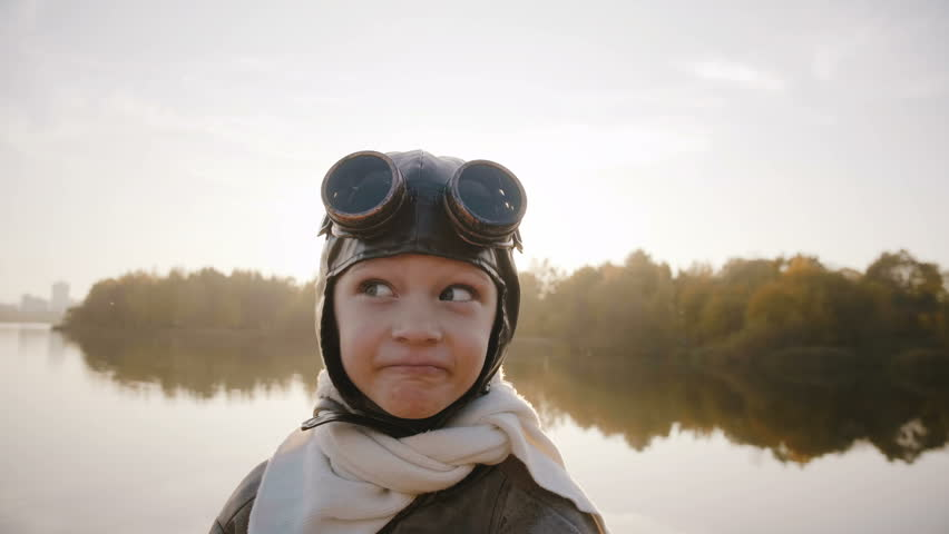 Little boy in vintage pilot costume with scarf and glasses looking at camera making funny faces near lake slow motion. | Shutterstock HD Video #1020807946