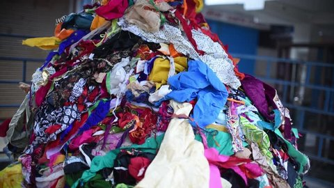 A pile of waste clothes thrown in trash, it could be used in recycling and given to poor