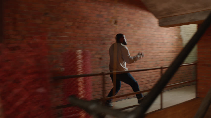 Camera chases angry man up an industrial staircase where two enemies begin to fight in moody lighting. Medium shot in 4K with an Alexa Mini camera