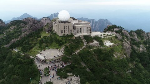 HUANGSHAN, CHINA - SEPTEMBER 2018: Tilting aerial footage of weather station located on strategic mountain peak in Huangshan national park, scientific facility and tourist attraction in China