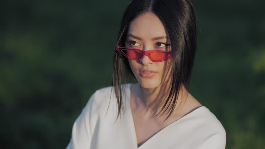 Fashion asian model portrait with creative stylish make-up wearing trendy red sunglasses white silk fashion japanese kimono sitting against blurred nature backgroung. 4k slow motion footage   Shutterstock HD Video #1020885076