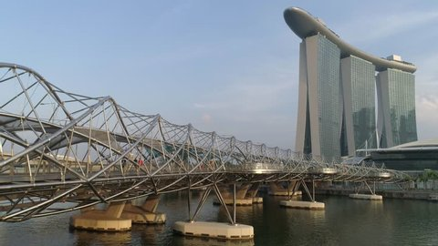 Singapore - June 28, 2018 : Concrete covered with stainless bridge to Marina Bay Sands Hotel in a cloudy day in Singapore. Singapore city in the daytime. The Helix Bridge and Marina Bay Sand in