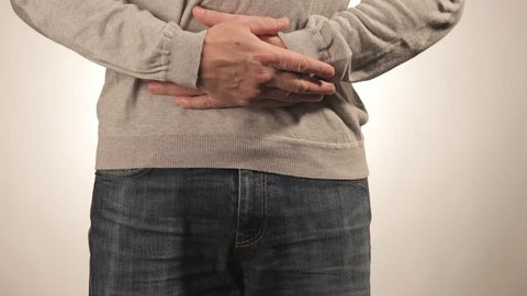Man holding his stomach in pain. Men problems on white background. Medical concept