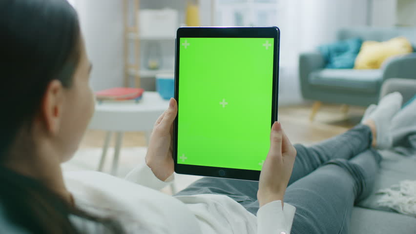 Young Woman at Home Resting on a Couch Using with Green Mock-up Screen Tablet Computer in Vertical Portrait Mode. Woman Using Tablet Device, Browsing Internet, Watching Content, Videos. | Shutterstock HD Video #1020934096