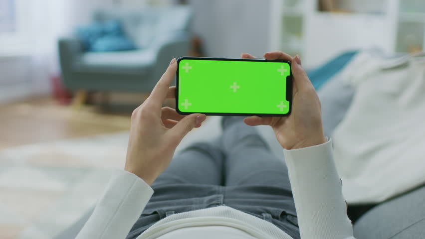 Young Woman at Home Lying on a Couch using with Green Mock-up Screen Smartphone in Horizontal Landscape Mode. Girl Using Mobile Phone, Browsing Internet, Watching Content, Videos, Blogs. POV.