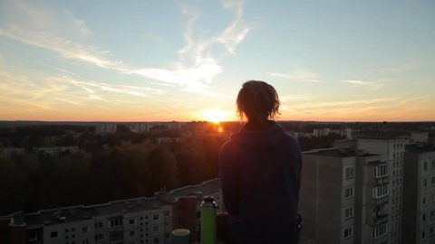 Young man sitting on the edge of the roof with a thermos flask and cup of tea overlooking beautiful sunset and city panorama. Urban soviet block of flats and forest in the background.