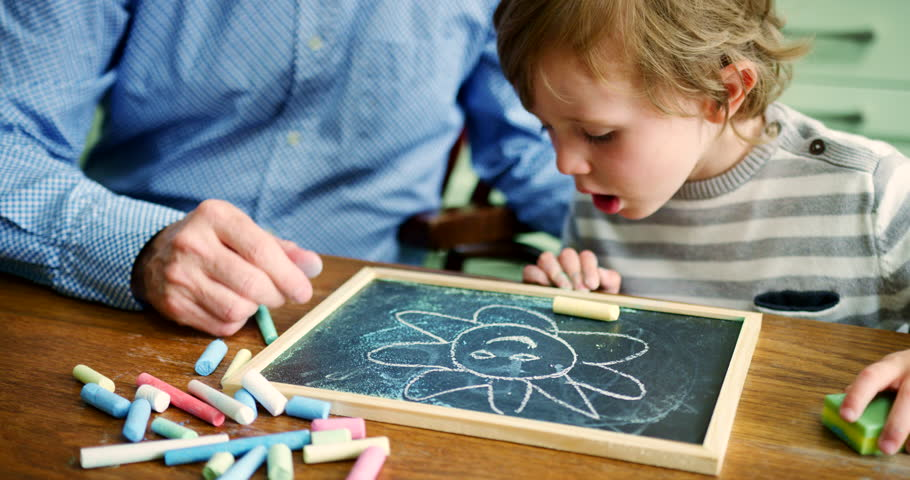 Father helping young boy to learn to draw using blackboard and chalk. Boy is blowing chalk dust. Close up shot. Educational concept parenting childhood. Slow motion. Shot on RED Camera. | Shutterstock HD Video #1020987946