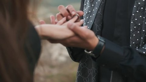 A Young Man Puts A Engagement Ring On The Finger Of A Woman And Kisses Her Hand With Love. Man Is Wearing Black Stylish Clothes. A Young Woman Made A Manicure With Long Nails, A Beautiful Pink Color