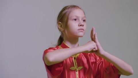 Teenager girl do kung fu greeting two hands together with right fist on the left palm is the Wushu Tai Chi Chinese Martial Art greeting. Red yifu clothes . Salutation in Kung Fu at grey background