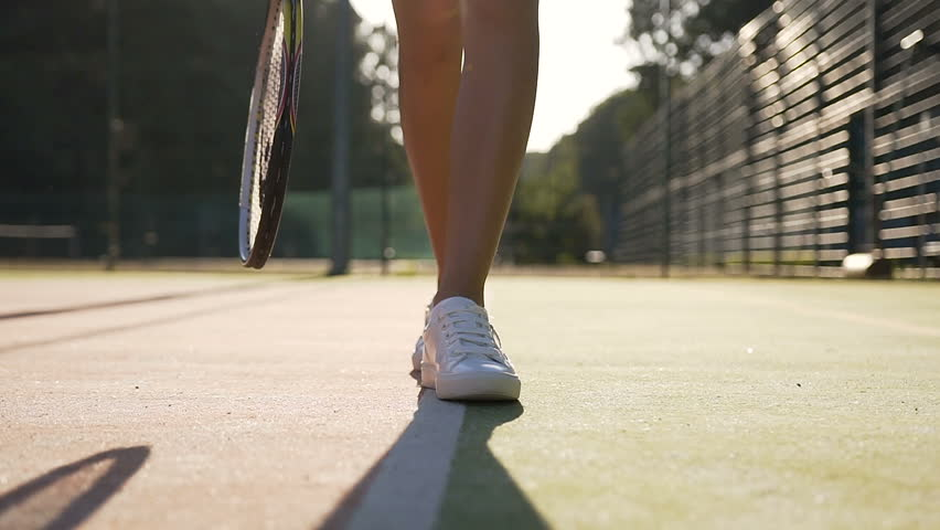 Close up shot of female tennis player legs in white sneakers with tennis racket walking on the court. Outdoor shooting. #1021040176