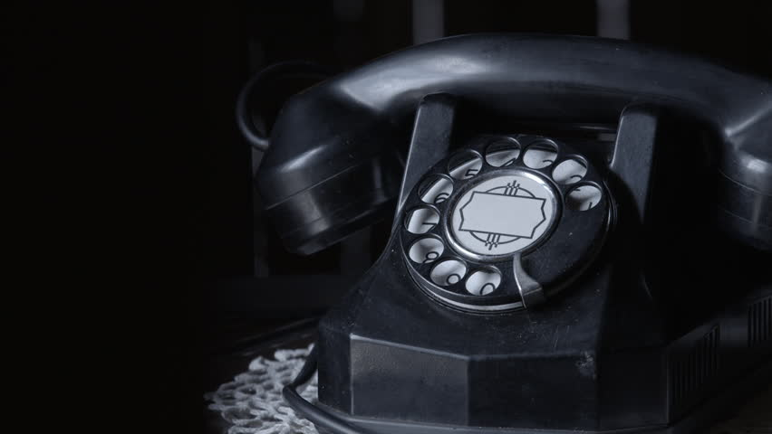 Historical old rotary telephone on table in darker room. Picks up phone to answer a phone call - Makes a call, dials rotary phone.