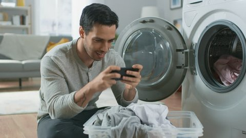 Handsome Smiling Young Man in Grey Jeans and Coat Sits in Front of a Washing Machine and Plays Games on His Smartphone. He Loads the Washer with Dirty Laundry. Living Room with Modern Interior.