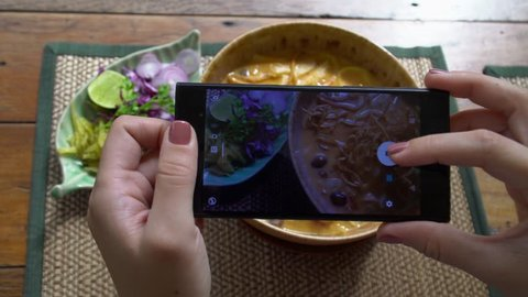 Taking Mobile Picture of Traditional Lanna Style Dish - Khao Soi Soup with Crispy Noodles. Food Photo of Authentic Nothern Thai Cuisine