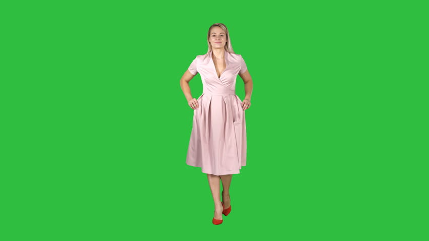 Woman in pink dress with hands in pockets is walking towards the camera on a Green Screen, Chroma Key.