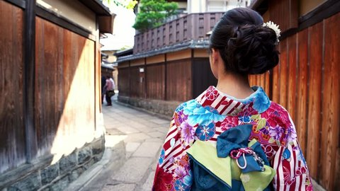 Kyoto, JAPAN - APRIL 20, 2018: down to up back view of young japanese woman in kimono dress walking in ishibe alley and meet people in traditional clothing standing in middle of street.
